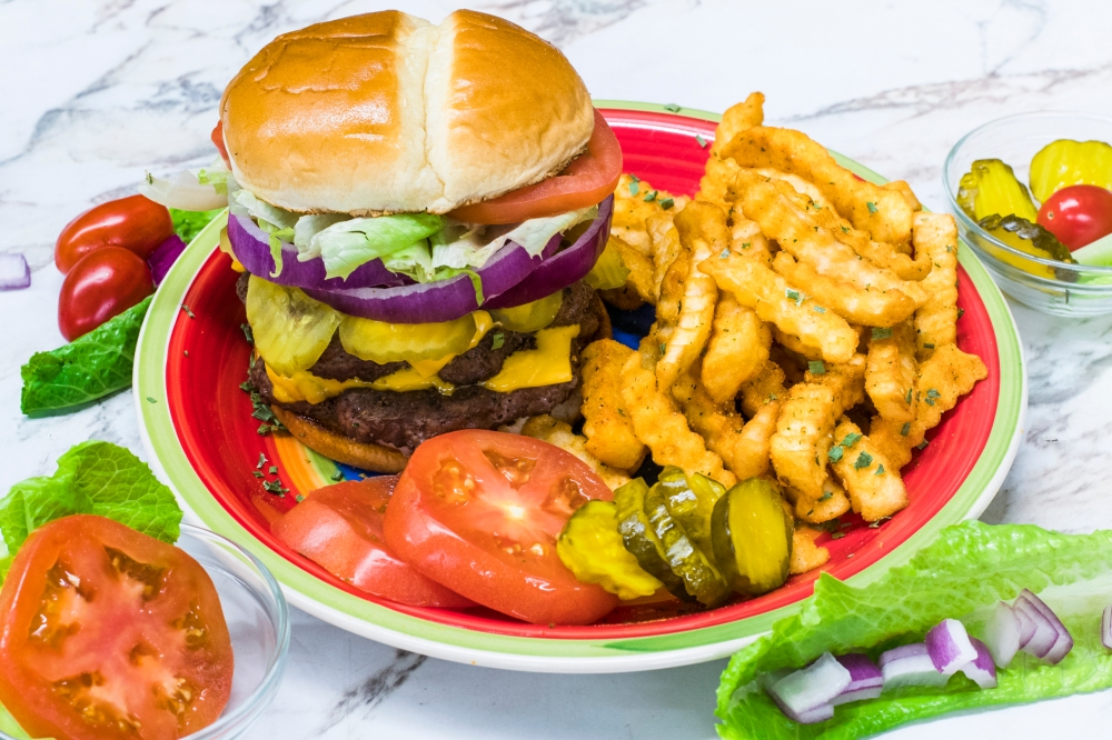 cheeseburger with lettuce, onion, tomatoes and pickles for delivery